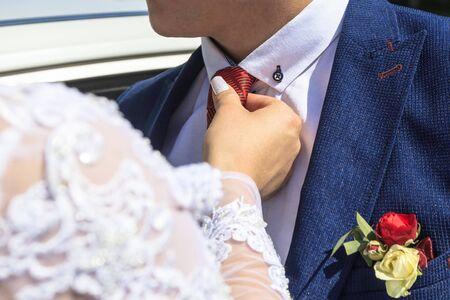 Tageslicht. Braut glättet die rote Krawatte des Bräutigams. Tonen haben. Standard-Bild