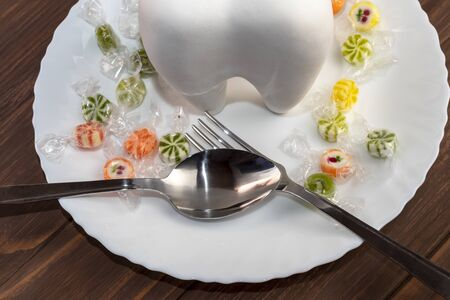 wooden background with a big tooth on a plate. in a spoon a lot of sweets. there is a plug. Banque d'images - 129311951