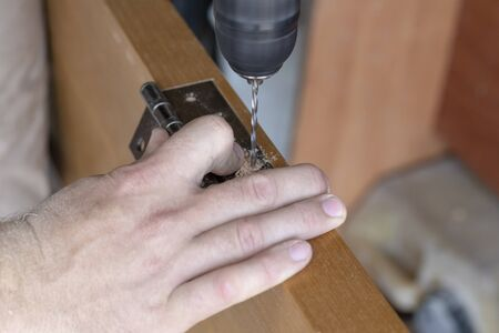 the master sets the door hinge. drills a hole with a tool. Stockfoto