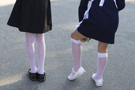 Settembre. inizio anno scolastico. vista posteriore. la ragazza raddrizza le calze bianche