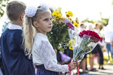 blonde girl holding flowers in her hands. the beginning of the school year. first call