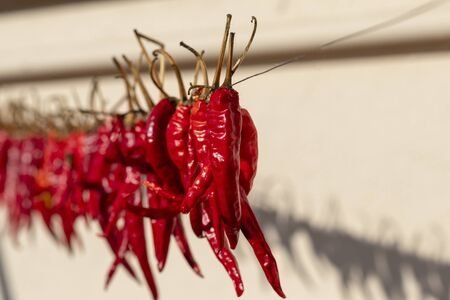daylight. red pepper dries on a rope in the street. there is tinting Stockfoto