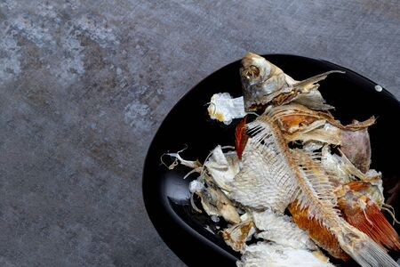 wooden background. a plate of dark color. there are bones from eaten fish Stok Fotoğraf - 129922745