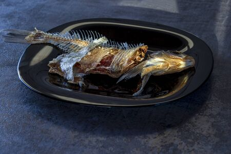 wooden background. a plate of dark color. there are bones from eaten fish
