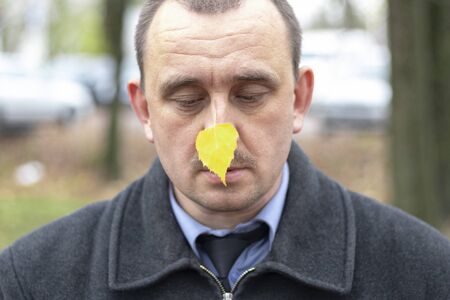 a man looks at a yellow leaf of birch. wearing a coat, have a tie
