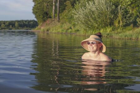 girl in a straw hat, she is in the lake. only the head is visible looking into the distance. Stock fotó