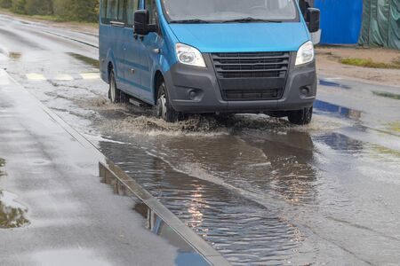 street lighting. its raining. a puddle formed on it a car will pass