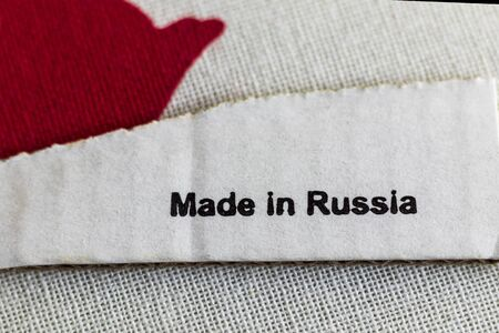 macro. a small piece of cardboard on it the inscription is made in Russia. burlap texture
