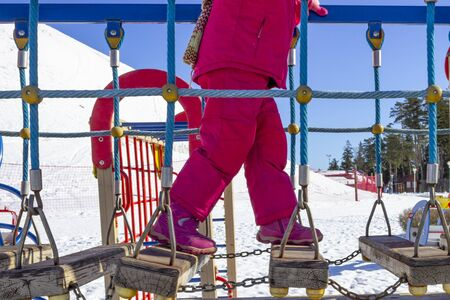 winter, cold, snow. a girl in a pink suit is walking up the stairs. they are made of wood and swing