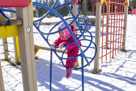 winter, cold, snow. little girl in metal rings at the playground