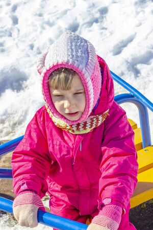 winter, cold. little girl in a pink jacket plays on the street. holds swing and gets angry Banco de Imagens