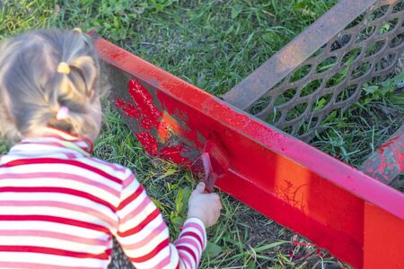 sunset. Blond girl paints a metal ladder with a brush. color is red. there is a shutter. soft focus. tinting.