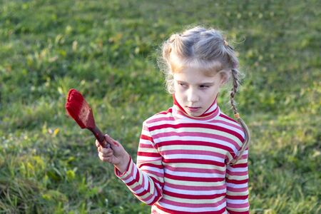 daylight. a little girl with white hair in her hands holds a red brush and looks at her
