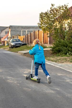 back view. girl in a blue jacket riding a scooter. blond hair color. she rolls her foot on the board