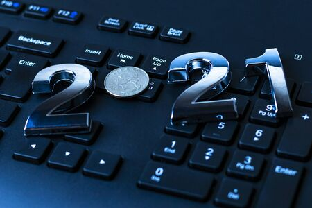 black keyboard close-up. on it are laid out numbers of metal 2021 in the center of the coin 0.25 dallar