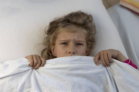 little girl with white hair. she hid under a blanket. scared look