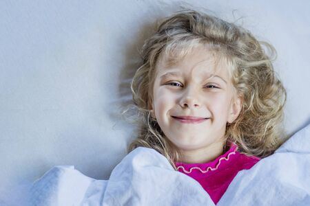 baby girl with blond hair. she lies in bed under a blanket. she smiles and looks at us Standard-Bild - 133958283