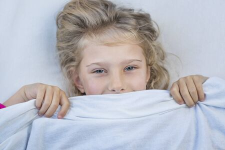 baby girl with blond hair. she lies in bed under a blanket. she smiles and looks at us Standard-Bild - 133958285