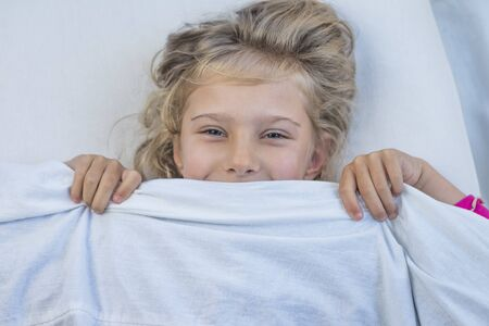 baby girl with blond hair. she lies in bed under a blanket. she smiles and looks at us