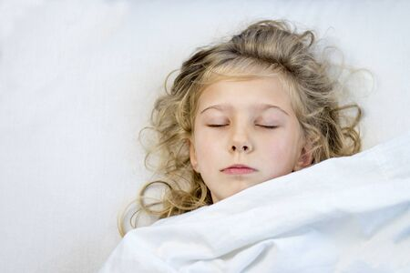 a girl with blond hair she lies in bed under a blanket. she fell asleep