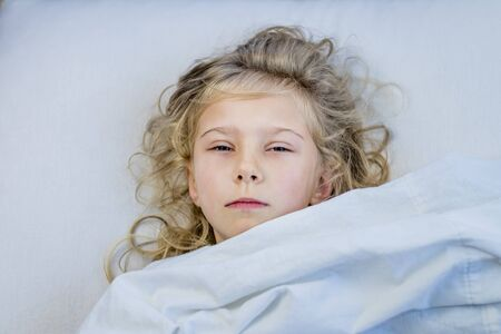 a girl with blond hair she lies in bed under a blanket. she is sad.