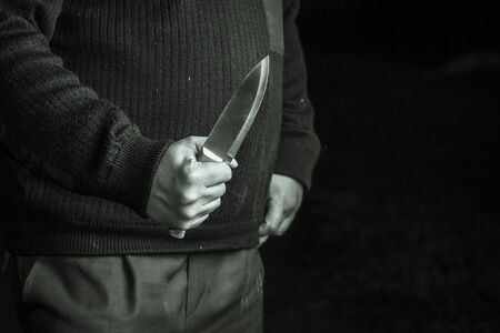 full night. a man holding a knife. close-up. concept of violence Banco de Imagens