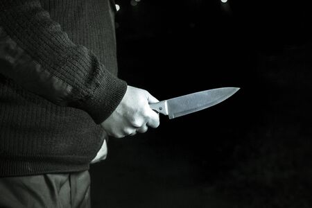 full night. a man holding a knife. close-up. concept of violence 版權商用圖片