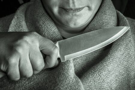 full night A man holds a knife at the girls throat. close-up. concept of violence