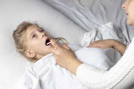a girl with white hair lies in bed. mom using an inhaler makes an injection in the throat of a patient