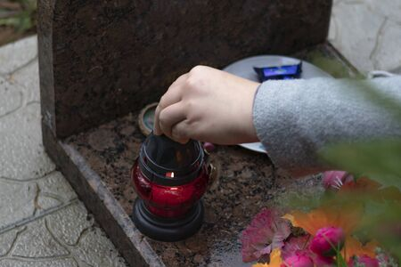 its raining. girl lights a candle. background grave. marble slab Banco de Imagens