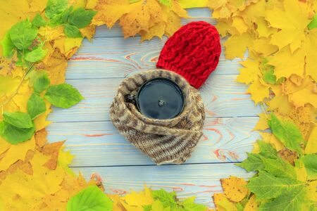 wooden background. yellow leaves around. in the center is a cup of tea, around a scarf and a red hat