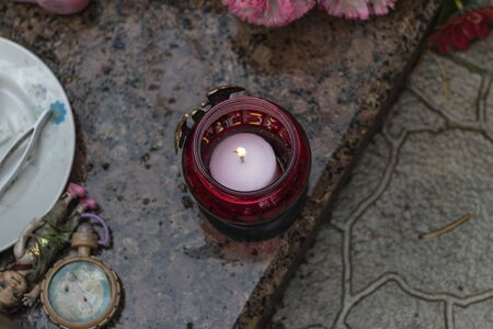 its raining. the candle is burning. background grave. marble slab