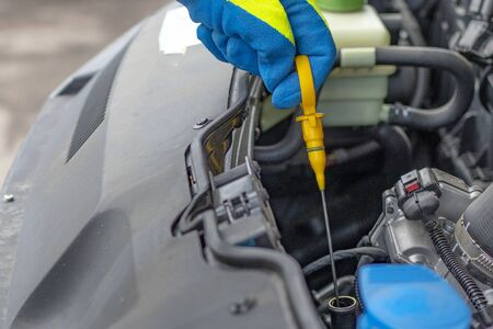 A male hand in a yellow glove pulls out an oil dipstick. checking the oil level.
