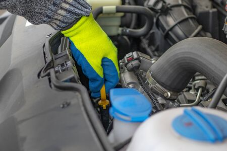 A male hand in a yellow glove holds the lid. checking the oil level. Banco de Imagens