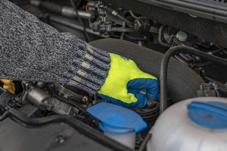 A male hand in a yellow glove holds the lid. checking the oil level. 版權商用圖片