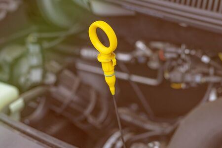 open car hood. get the probe. it is yellow. checking the oil level. Stockfoto