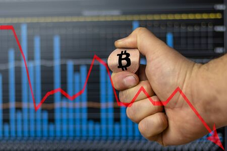 a man holds a bitcoin coin in his hand and bent it. but a background of graphs. concept does not withstand the pressure on him and falls.