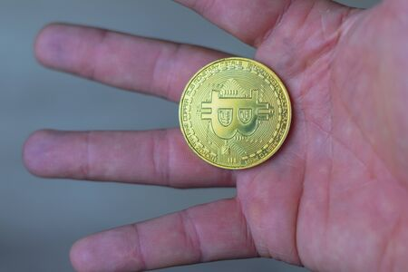 man holding a bitcoin coin in his hand. schedule close-up Stock fotó - 133958013