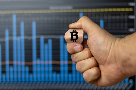 a man holds a bitcoin coin in his hand and bent it. but a background of graphs. concept does not withstand the pressure on him and falls. Stock fotó - 133958023