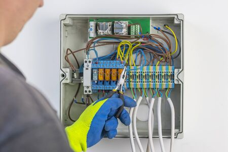 with the help of wire cutters, the master places the wire in the socket. panel board. not only electricity and internet control are mantled into it