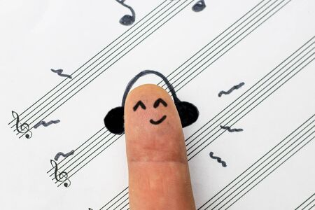 concept. finger lies on notes and listens to music. he is satisfied