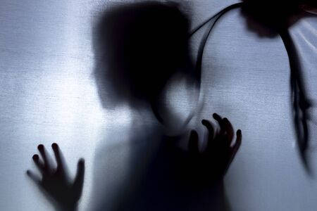 no focus. the fabric behind her. silhouette and shadow. child over head strap. domestic violence concept
