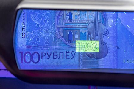 banknote of 100 rubles. located in an ultraviolet lamp.