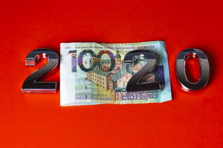 100 rubles a bill. on an orange background. The numbers 2020 with a metallic sheen are laid out. close-up