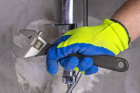 close-up. the master clamps the nut. fasten the tap to the wall