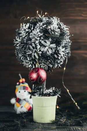creative tree of small stature. the garland is on. the snowman is out of focus. have tinted