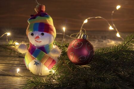 Snowman is not big, on a wooden background. he is wearing a scarf and hat. Christmas tree decoration at the bottom of the spruce Foto de archivo