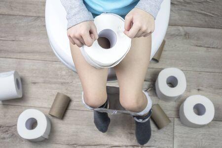 Das Kind sitzt auf einer weißen Toilette. in seinen Händen ist Toilettenpapier. auf dem boden liegen viele rollen. Nahaufnahme