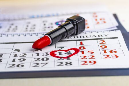The calendar. He is wearing red lipstick in a black case. February 14th is in a circle. Close-up.