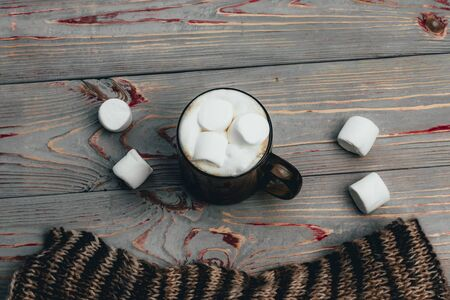 Marshmallow. Retro style wooden background. Glass mug with marshmallow in it. There is also a woolen scarf. Close-up. Tinted. Фото со стока